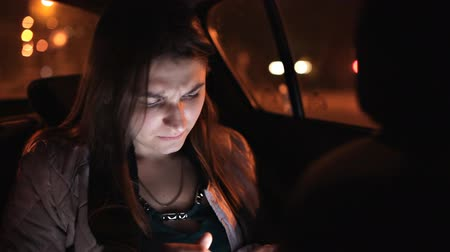 black cab : Beautiful business woman traveling in a taxi to an important meeting and corresponding with colleagues using a smartphone Stock Footage