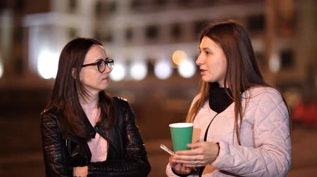 consumir : Two young girls walk through the old town at night and chat, drink hot coffee