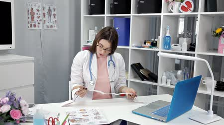 psiquiatra : Young woman doctor sits in her office and retrieves test results
