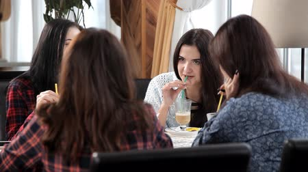 chatter : four girls drink a latte or coffee at a cafe laughing and talking. bachelorette party with coffee. coffee-break