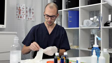 vestindo : Doctor put on blue latex gloves, closeup.Doctor disinfects hands