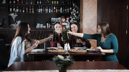 повод : several girls eat pizza and drink beer from bottles in the restaurant. Talk laugh and celebrate Стоковые видеозаписи