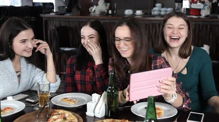 társ : several girls eat pizza and drink beer from bottles in the restaurant. Talk laugh and celebrate Stock mozgókép