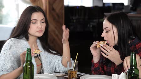 bachelorette party : several girls eat pizza and drink beer from bottles in the restaurant. Talk laugh and celebrate Stock Footage