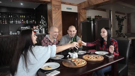 повод : a group of young people drink beer and eat pizza in a restaurant