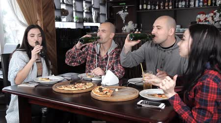 összejövetel : a group of young people drink beer and eat pizza in a restaurant