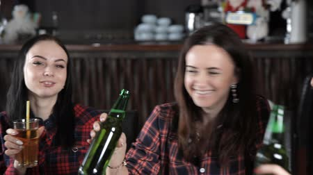 companionship : several girls eat pizza and drink beer from bottles in the restaurant. Talk laugh and celebrate Stock Footage