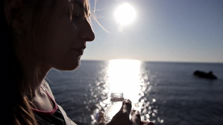 hydratace : Woman drinking from a Water Bottle near sea