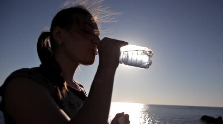 hidrasyon : Woman drinking from a Water Bottle near sea