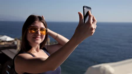 water display : An attractive young woman using a smartphone at the beach, a woman is photographing a sunset by the sea. Stock Footage