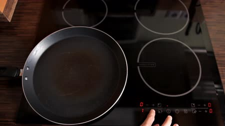 ノブ : The girl turns on the stove for cooking in the kitchen