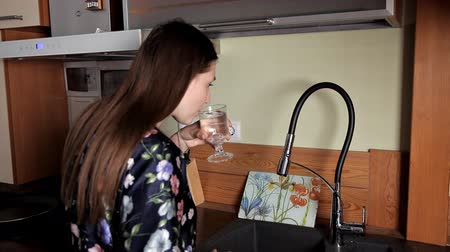 закалки : Girl getting a glass of water from the tap in the sink and drinking