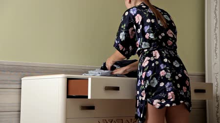 kasten : A young girl folds work clothes into a chest of drawers