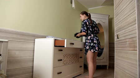 kasten : A young girl lays out clothes from a dresser and goes to try on her Stockvideo