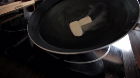 スプレッド : The girl spreads butter on a red-hot skillet. Cooking breakfast