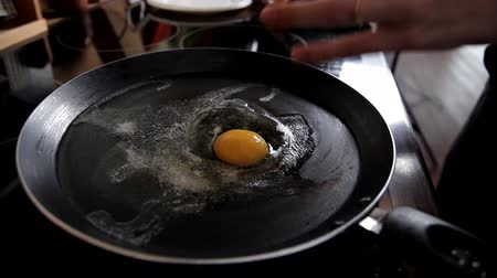 omlet : In the morning the girl prepares breakfast at home in the kitchen, breaks eggs in a frying pan. Close-up. Cooking eggs at home in the kitchen
