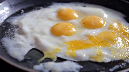 卵黄 : In the morning the girl prepares breakfast at home in the kitchen. Cooking eggs at home in the kitchen. Close-up