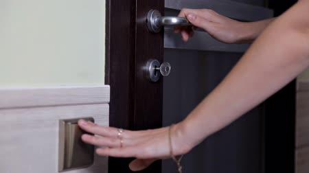 buraco de fechadura : The girl opens and closes the door to the apartment. The person using the key and locking the door of the apartment Stock Footage