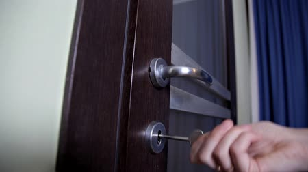 buraco de fechadura : Opening or locking a door lock with a key by woman