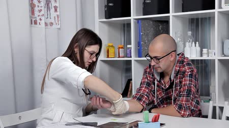 avaliação : The doctor examines a man whose hand injury
