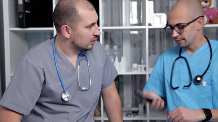 pánik : Male doctor and young intern in a good mood talking about new medical researchs
