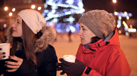 christmas tree with lights : Young girls are drinking coffee Winter weather outside. Coffee break. Christmas