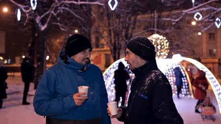 porcelana : Two men drink coffee in the winter evening in the park in the winter near beautiful Christmas decorations