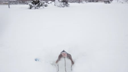 tágas : Young girl rejoices in the winter and snow, plays in the winter park Stock mozgókép