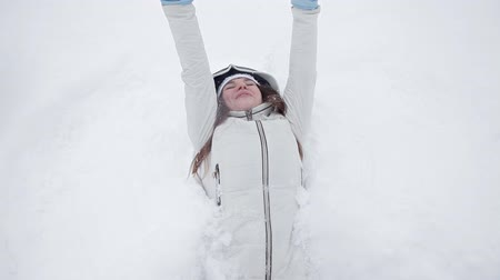 snow angel : A young girl rejoices in winter and snow, plays in a winter park, does not lie in snow Stock Footage