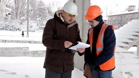 строительные леса : The customer, a business man, discusses the construction of his new shopping center with the architect and engineer. Plan, work