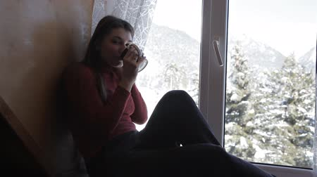 pletený : Cozy winter lifestyle. Young happy woman drinking cup of coffee wearing knitted sweater sitting home by the big window with winter snow tree background Dostupné videozáznamy