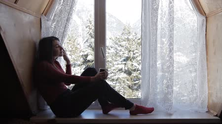 happy socks : Cozy winter lifestyle. Young happy woman drinking cup of coffee wearing knitted sweater sitting home by the big window with winter snow tree background Stock Footage