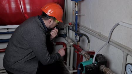 pressão : Technician inspecting heating system in boiler room