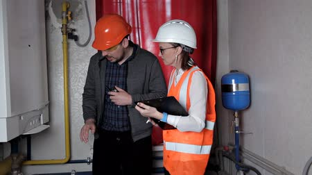 heating system : The inspector and the worker check the heating system. Beautiful woman engineer