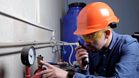 gas : An engineer in glasses works in the boiler room, checks the maintenance of the heating system equipment Stock Footage