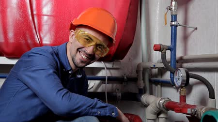 heating system : An engineer in glasses works in the boiler room, checks the maintenance of the heating system equipment Stock Footage