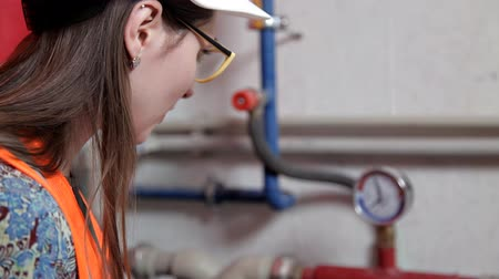 termostat : Female engineer checks the data of the heating system equipment in the boiler room