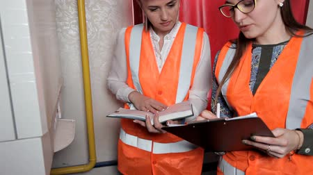 termostato : Two woman engineers checking technical data of heating system equipment in a boiler room