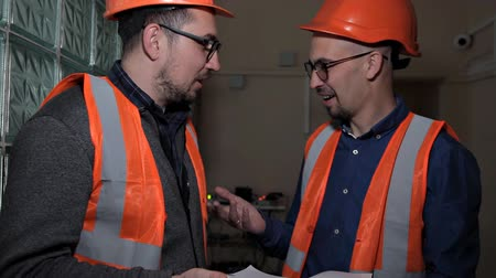 supervising : Two engineers discuss and make notes about the system check done Stock Footage