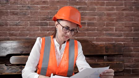 прораб : Young female engineer takes notes on work.Special uniform and helmet Стоковые видеозаписи