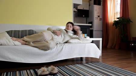 probudit se : A young girl fell asleep on the sofa in home clothes. Woke up after sleep