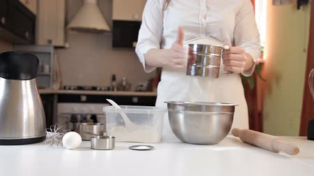 sifting : Young woman in white apron sifting flour for making pizza dough