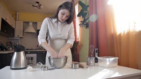 kneads : A young girl kneads a pizza dough with her hands. Home, Food, Baking, Apron