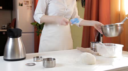 levedura : A young girl in the kitchen prepared the dough. Dough on the table