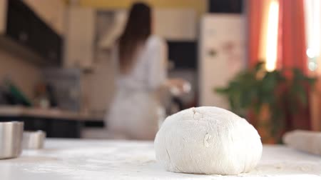 дрожжи : A young girl in the kitchen prepared the dough. The dough on the phone