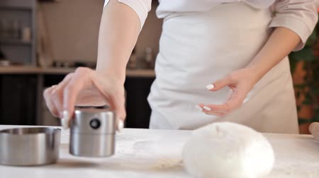 gevonden : A young girl in the kitchen prepared the dough. Dough on the table