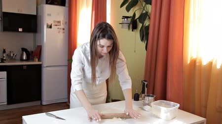 fartuch : Girl in an apron preparing raw pizza dough. The girl is preparing a delicious pizza at home. Pastry