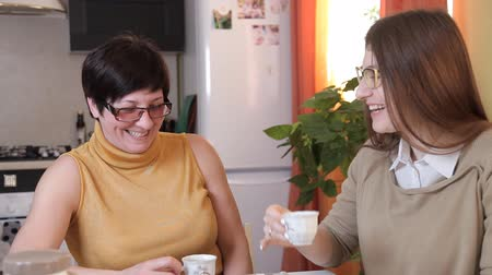 зрелом возрасте : mom and young daughter with glasses drink tea or coffee in the kitchen and eat cakes, talk, laugh Стоковые видеозаписи