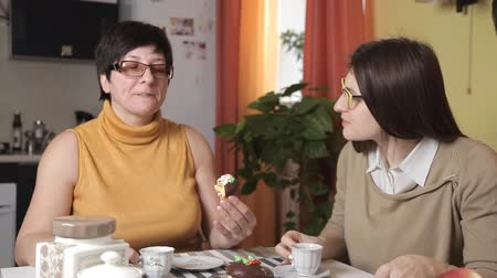 зрелом возрасте : Mom eat cake is well plastered with cream and her daughter wipes