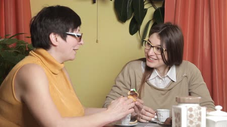 зрелом возрасте : The mother eats the cake and her daughter drinking coffee. Kitchen, laughter, conversation. Women with glasses